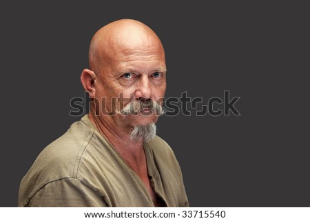 A sinister looking man in a green shirt - stock photo