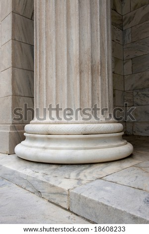 A sinlge white stone column with groves and designs