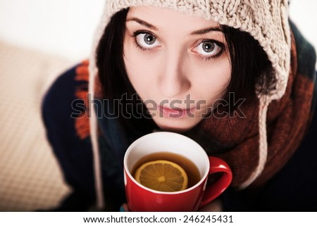 A sip of hot coffee in the winter. A girl in a knitted hat holding a red cup of tea with lemon - stock photo