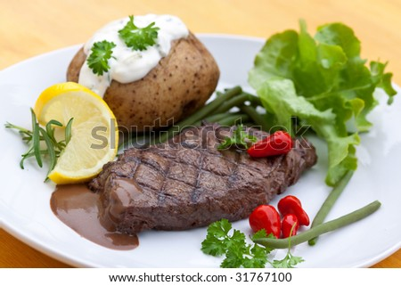 a sirloin strip steak with vegetables and savory sauce - stock photo