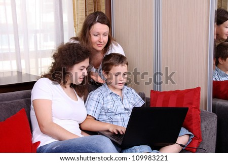 A sister and a brother  and their a mother with a laptop - stock photo