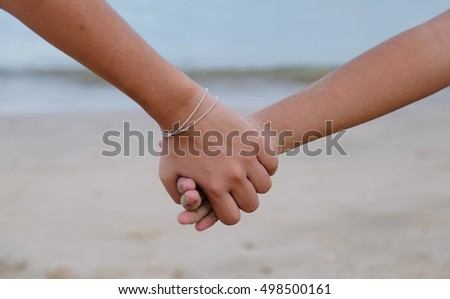 A sister holding her brother's hand on the beach in evening. showing care and love.