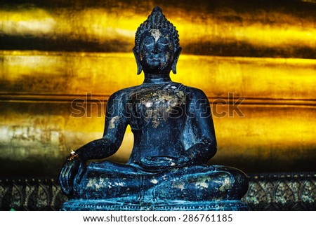 A sitting Buddha statue at the feet of the reclining Buddha at Wat Pho Thailand. - stock photo