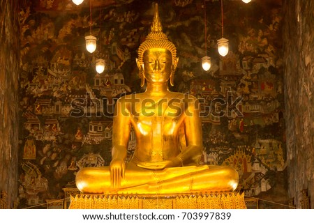 A sitting golden Buddha statue in a public Buddhist temple in Bangkok, Thailand