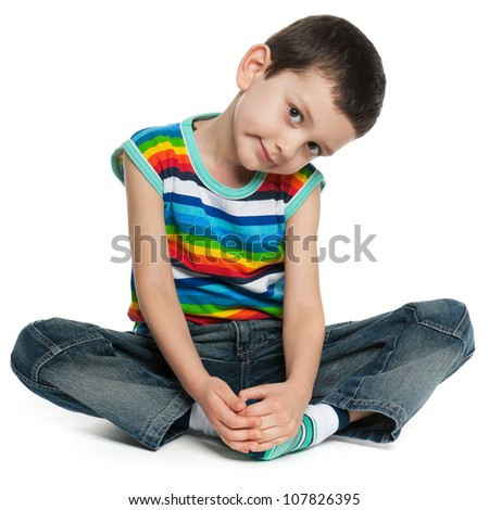 A sitting little boy in striped shirt; on the white background - stock photo