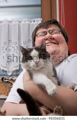 a sitting mentally disabled woman is holding a cat - stock photo