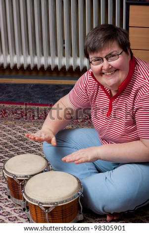 a sitting mentally disabled woman make music and looks excited - stock photo