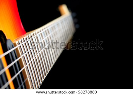 A six string electric guitar isolated on a black background - stock photo
