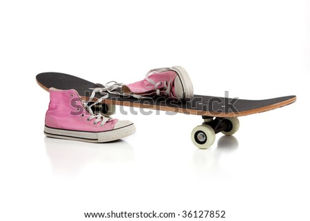 A skate board and pink sneakers on a white background with copy space