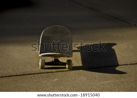 A skateboard sits in the sun. - stock photo