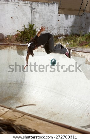A skateboarder carves a radical backhand grind in an empty swimming pool. - stock photo