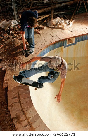 A skateboarder executes a radical move known as a rock n roll in an empty swimming pool as a videographer films him. - stock photo