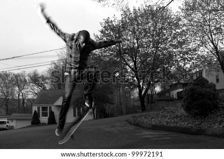 A skateboarder performs jumps or ollies on asphalt.  Slight motion blur showing the movement on the arms and legs. - stock photo