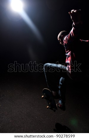A skateboarder performs tricks under dramatic low key lighting with bright lens flare. Shallow depth of field. - stock photo