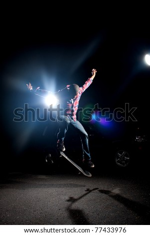 A skateboarder performs tricks under dramatic rim lighting with lens flares and copy space. - stock photo
