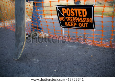 "A skateboarder steps over a fence with a sign that reads ""Posted No Trespassing Keep Out"". - stock photo"