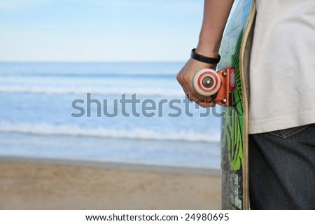 A skater holding his board. Beach background with plenty of copy-space.