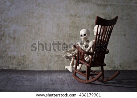 A skeleton and a little skeleton sitting in the rocking chair in a grungy room - stock photo