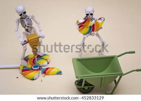 A skeleton breaking lollipop to pieces while other moving it - stock photo