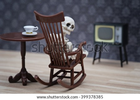 A skeleton on rocking chair looking back while watching TV
