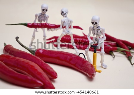 A skeleton pumping red chili, his two friends are helping - stock photo