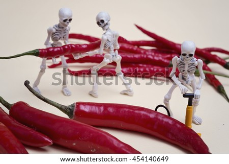 A skeleton pumping red chili pepper  - stock photo
