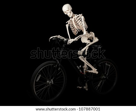 A skeleton rides a bicycle from nowhere. - stock photo
