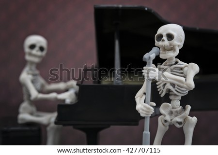 A skeleton singer with a skeleton pianist in the back