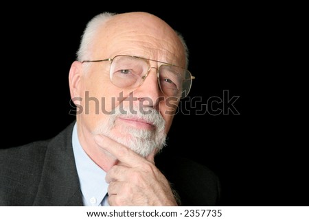 A skeptical looking, intelligent senior man over a black background. - stock photo
