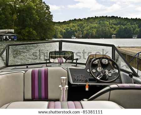 A ski boat tied up at a dock showing the interior view. - stock photo