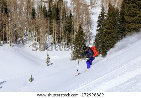 A ski guide descending a slope in the Utah mountains, USA. - stock photo