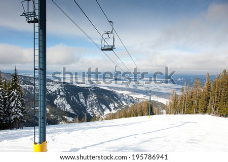 A ski lift going up a steep mountain covered with fresh snow and a valley behind with morning fog. - stock photo