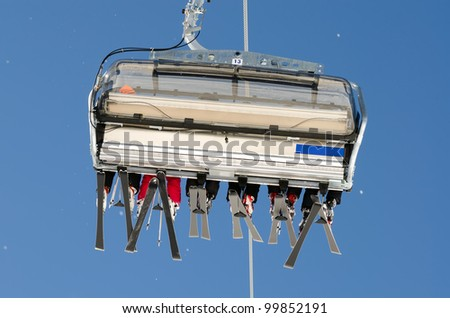 a ski lift with skiers before blue sky - stock photo