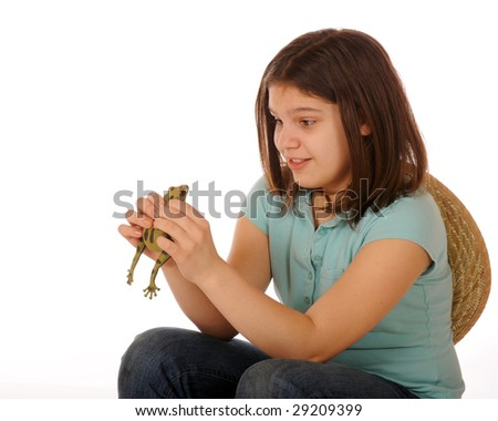 A skiddish preteen girl studying a spotted green frog as she holds him in both hands.  Isolated on white. - stock photo