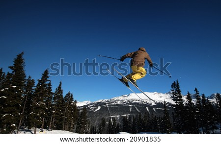 A skier coming in for a landing in Whistler, BC. - stock photo