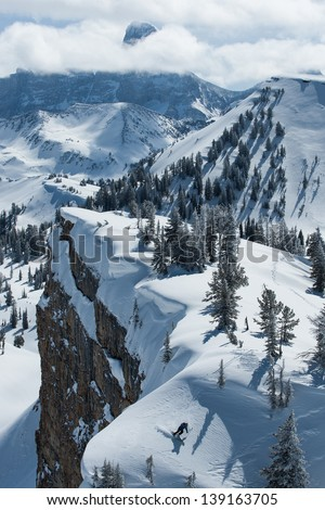 A skier finds a patch of power snow along side a cliff band at Grand Targhee Resort. - stock photo