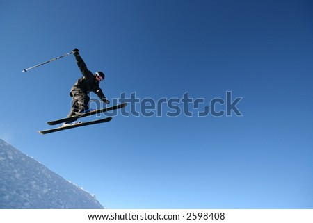 A skier in a business-like pinstripe ski suit flies through the air. - stock photo