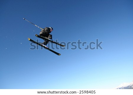 A skier in a business-like pinstripe suit flies through the air in Whistler, BC. - stock photo