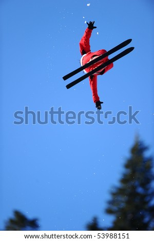 A skier in a red suit gets air during a trick. - stock photo
