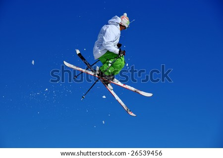 a skier in green and white performing a tele-heli, surrounded by snow which followed him from take-off - stock photo