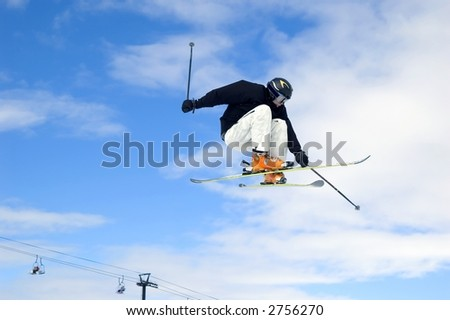 a skier jumping high through a blue sky - stock photo