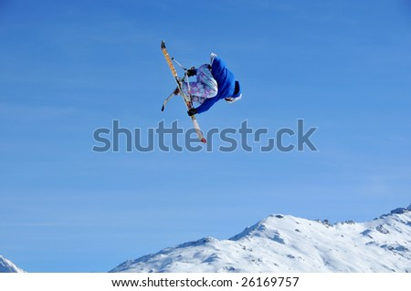 a skier jumping while crossing his skis and holding both of his skis in his hands.