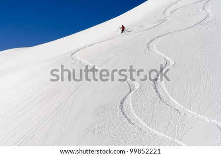 a skier makes his tracks in the deep powder snow - stock photo