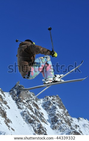 a skier performing a high jump with snow covered mountains in the background