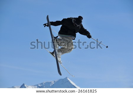 a skier with black clothes executing a jump and touching the end of one of his skis