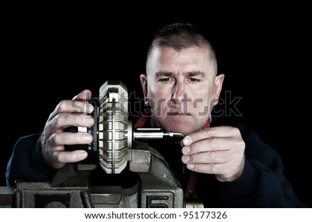 A skilled, adult male mechanic works on a new mechanical pump that includes a measurement scale - stock photo