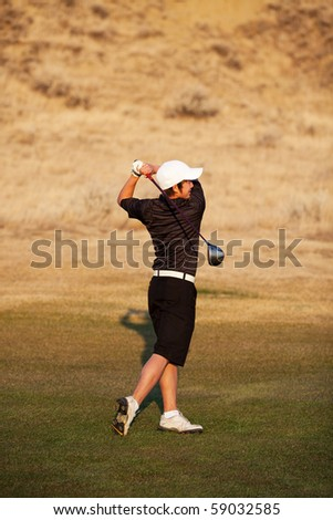 A skilled, mixed-race teenager playing golf.  Shot in early evening light. - stock photo