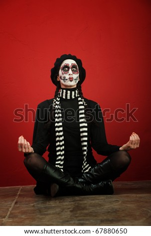 A skinny woman with All Souls Day makeup in a meditation pose - stock photo