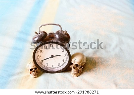 A skull and alarm clock on bedroom  - stock photo