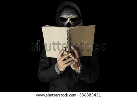A skull guy in black suit reading notebook, on black dark environment background - stock photo